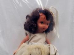 White doll with brown hair wearing a cream dress is in a bag pinned to the wall.